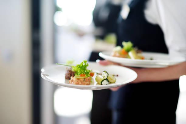 Kellner mit Tellern mit Fleischgericht – Foto