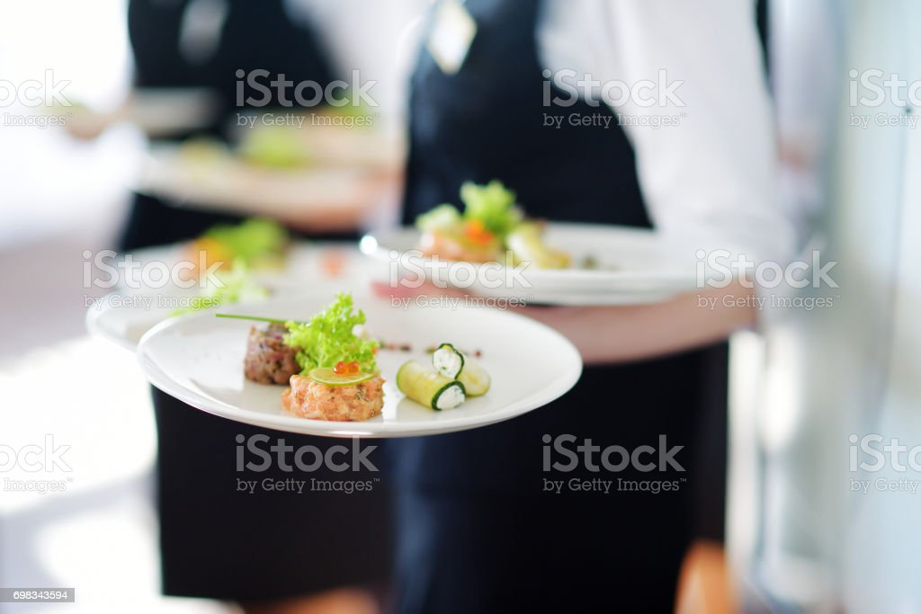 Waiter carrying plates with meat dish stock photo