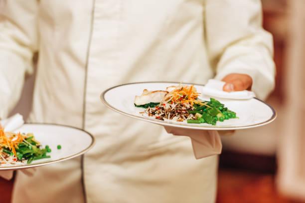 Kellner mit zwei Tellern mit Fisch und Reisgericht auf einer festlichen Veranstaltung, Party, Hochzeit oder Cater-Veranstaltung – Foto