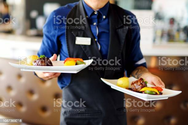 Waiter carrying two plates with meat dish on some festive event picture id1057369218?b=1&k=6&m=1057369218&s=612x612&h=lre49vq4t51pihnkgrtu5muw8kkzyrqkfduwzbfu4ji=