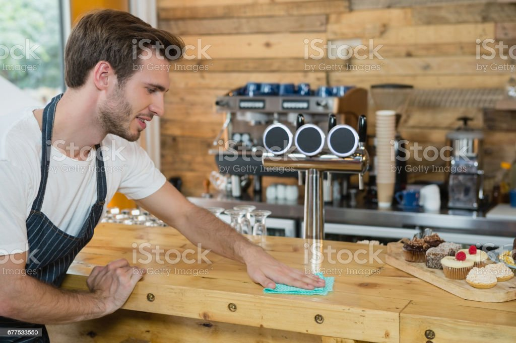 Waiter cleaning counter worktop royalty-free stock photo