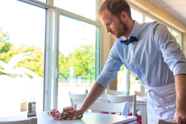 Waiter cleaning the table at restaurant stock photo