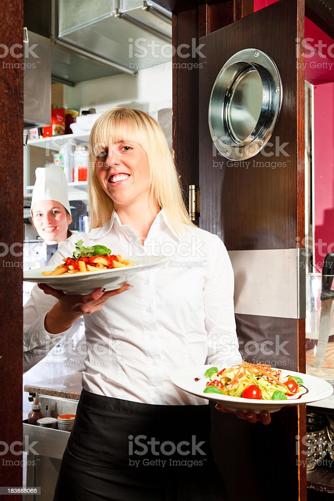 waiter coming out of the kitchen royalty-free stock photo