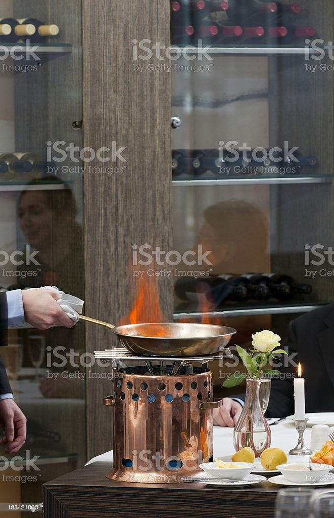 waiter cooking flambe crepes Suzette at restaurant table stock photo