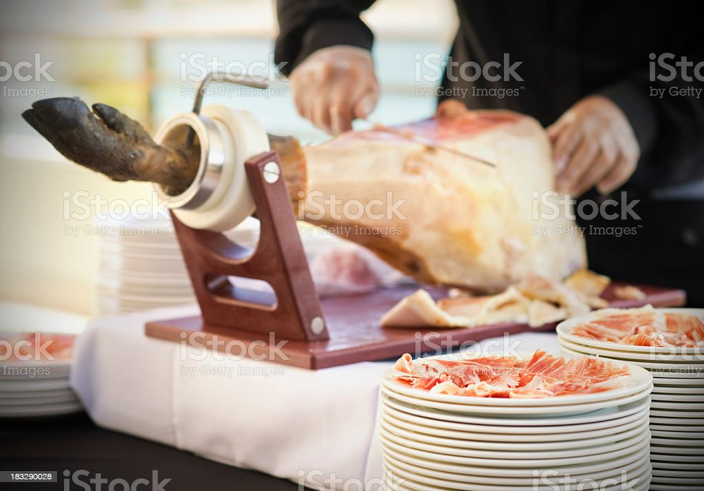 Waiter cutting slices of Spanish Serrano ham stock photo