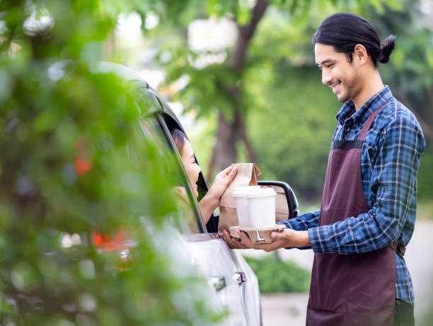 Waiter deliver food throght drive thru service stock photo
