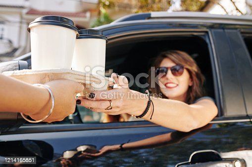 Waiter giving disposable tray with two cups of take out coffee to pretty smiling female driver