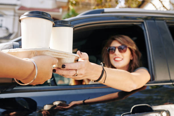 camarero dando tazas de café a conductor femenina - café bebida fotografías e imágenes de stock