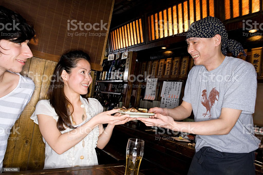 A waiter handing a woman a dish of yakitori royalty-free 스톡 사진