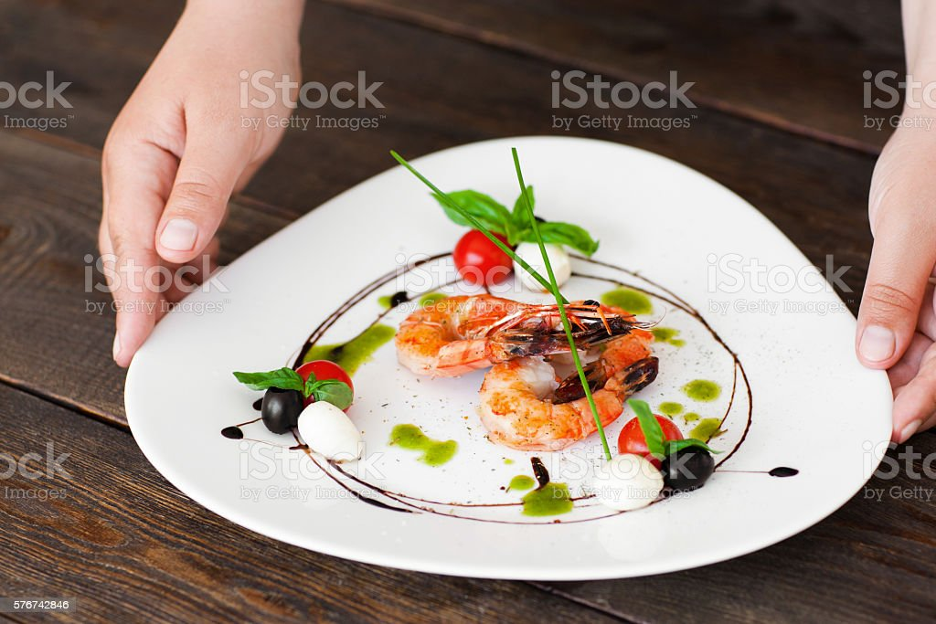Waiter hands put plate with shrimps on dark table stock photo