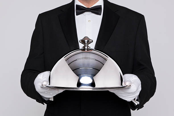 Waiter holding a silver cloche Waiter serving a meal under a silver cloche or dome waiter stock pictures, royalty-free photos & images
