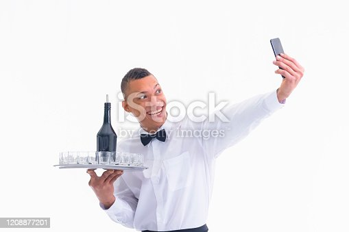 Handsome smiling young waiter using his phone while holding a tray with glass shots and a bottle on a light background. Work and service concept.