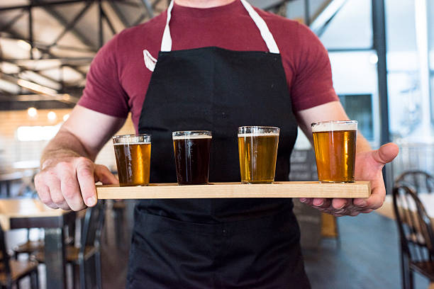 Waiter Holding A Tray Of Beer Tasting Glasses - foto stock