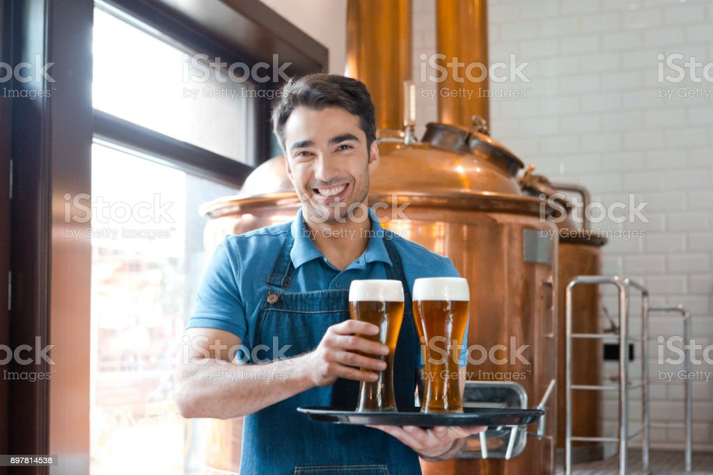 Waiter holding a tray with glasses of beer in brewery Portrait of smiling waiter holding a tray with glasses of beer in brewery Adult Stock Photo