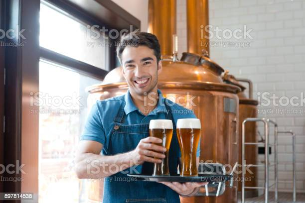 Waiter Holding A Tray With Glasses Of Beer In Brewery Stock Photo - Download Image Now