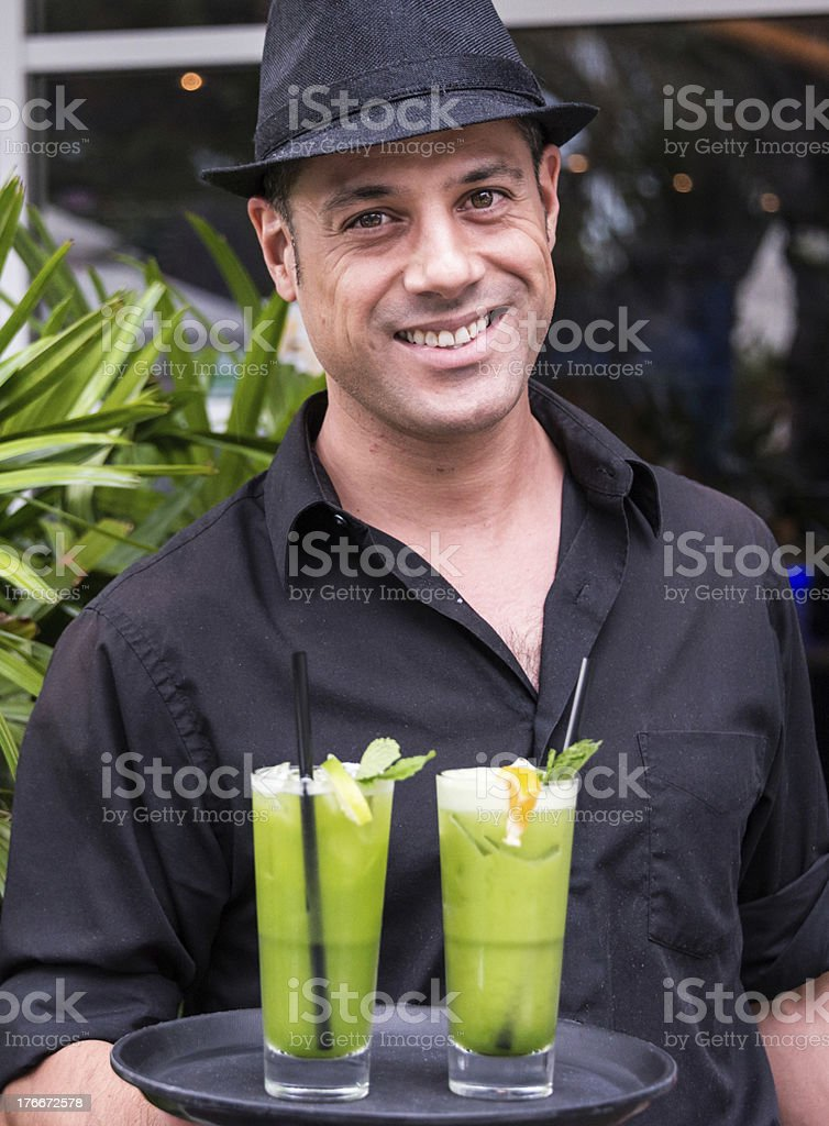 Waiter holding a tray with tropical cocktails royalty-free stock photo