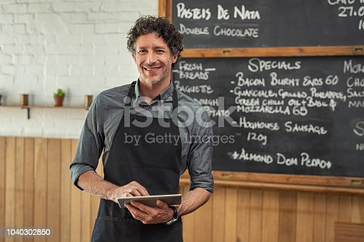 istock Waiter holding digital tablet at cafeteria 1040302850