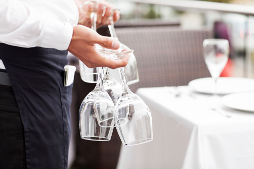 Waiter Holding Empty Wine Glasses In Restaurant