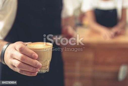 istock Waiter holding glass of tasty latte with tulip art 640293654