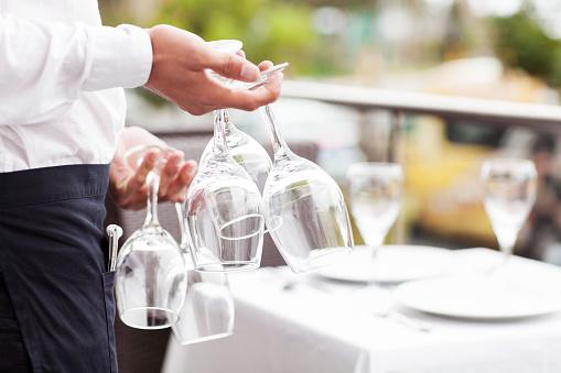 Waiter Holding Wine Glasses Upside Down In Restaurant
