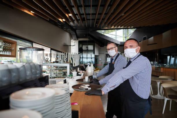 waiter in a medical protective mask serves  the coffee in restaurant - covid restaurant imagens e fotografias de stock