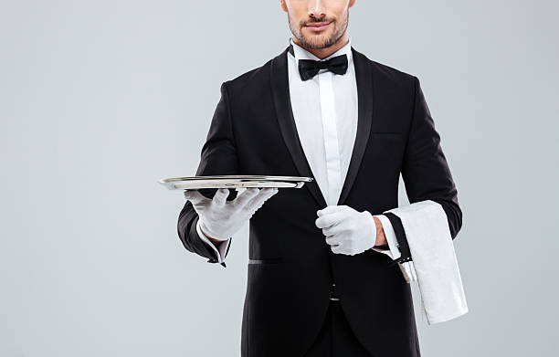 Waiter in tuxedo holding metal empty tray and napkin – Foto