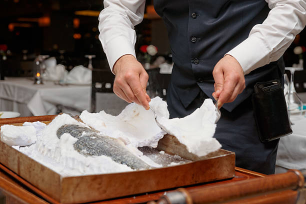 Waiter is carving fish baked in salt crust stock photo