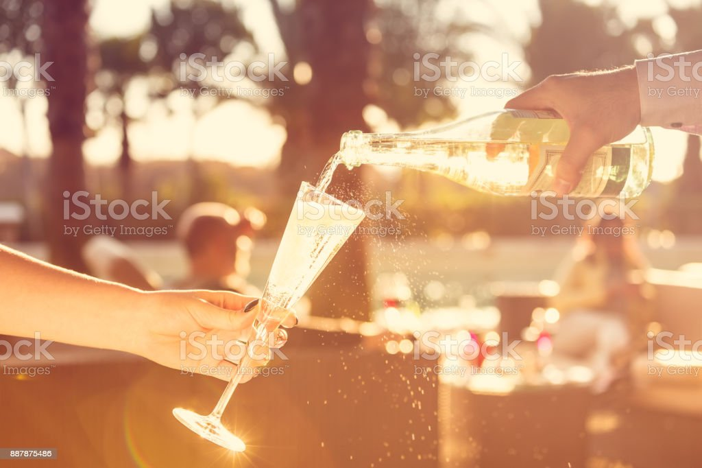 Waiter is pourring sparkling wine into a woman glass at the outdoor party.  Celebration concept stock photo