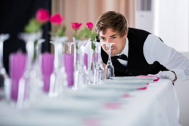 Waiter Looking At Table Arrangement stock photo