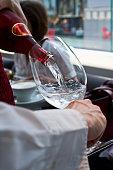 Waiter/ waitress pouring water. Macro, shallow focus.