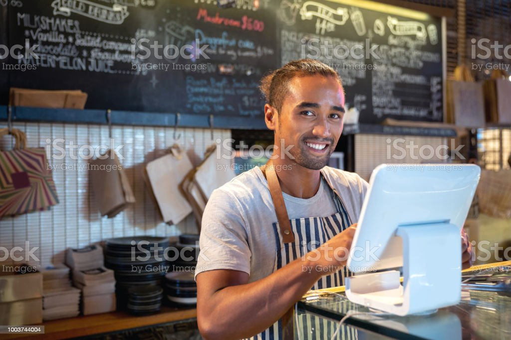 Waiter placing an order on the computer at a restaurant stock photo