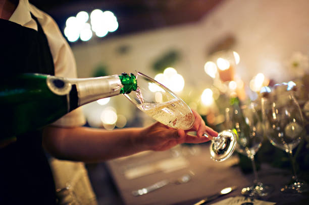 Waiter pour into a glass of champagne stock photo