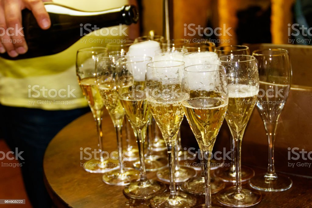 Waiter pouring champagne from a bottle into the glass. Close-up royalty-free stock photo
