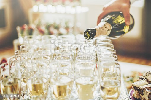 istock waiter pouring champagne in stylish glasses at luxury wedding reception. rich celebration. expensive catering and service at feast. new year and christmas celebrations and drinks 961793564