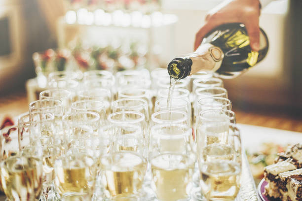 waiter pouring champagne in stylish glasses at luxury wedding reception. rich celebration. expensive catering and service at feast. new year and christmas celebrations and drinks - празднование годовщины стоковые фото и изображения