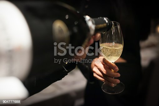 istock Waiter pouring champagne into the wine glass in restaurant. Blurry background 904777688