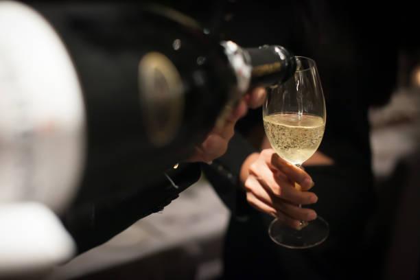 Kellner gießt Champagner in das Glas Wein im Restaurant. Unscharfen Hintergrund – Foto