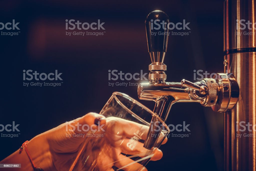 Waiter pouring draught beer into a glass - foto stock