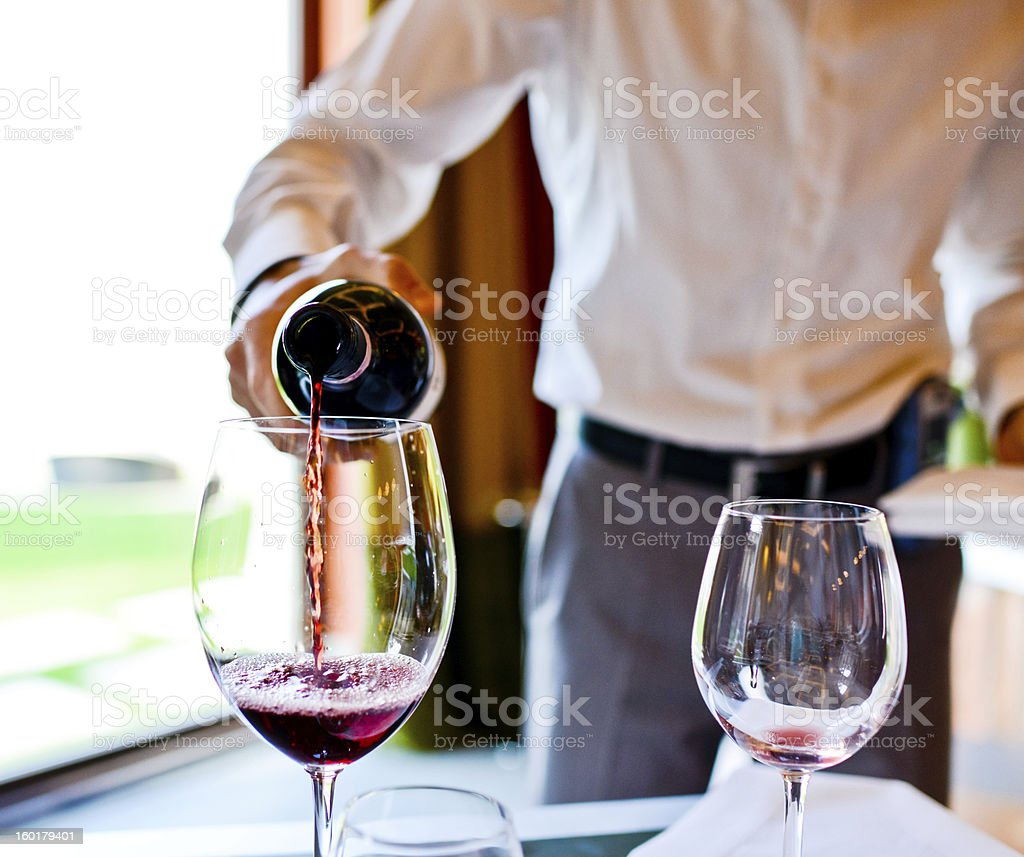 Waiter pouring Red wine in glass stock photo