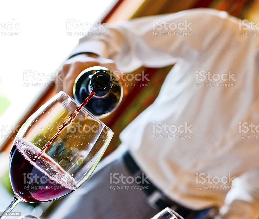 Waiter pouring Red wine in glass royalty-free stock photo