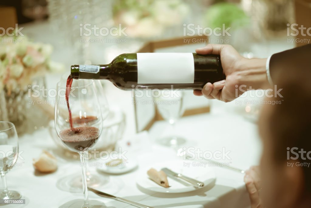 waiter pouring red wine in wine glass on the table for service in luxury dinner party, Blurry background with vintage color style. stock photo