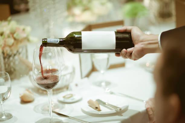 garçom derramamento de vinho tinto no copo de vinho na mesa para serviço de jantar de luxo, fundo desfocado com estilo vintage cor. - fine dining - fotografias e filmes do acervo