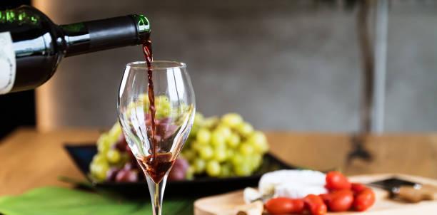 Camarero vertiendo vino tinto en una copa de vino. - foto de stock