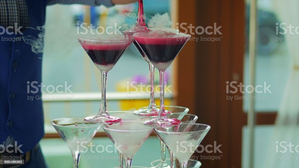 Waiter pouring red wine or champagne into glasses with liquid nitrogen for party. Young man pours wine into the pyramid from the glasses stock photo