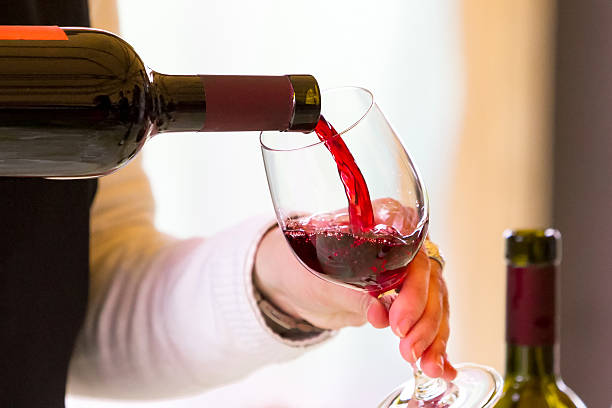 Waiter pouring red wine stock photo