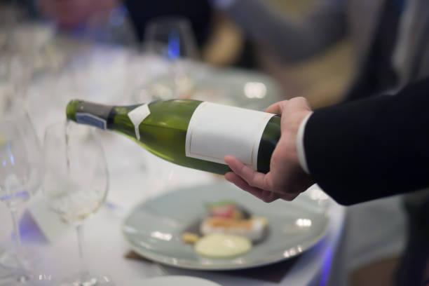 Kellner, Gießen Weißwein in das Glas Wein im Restaurant. Unscharfen Hintergrund – Foto