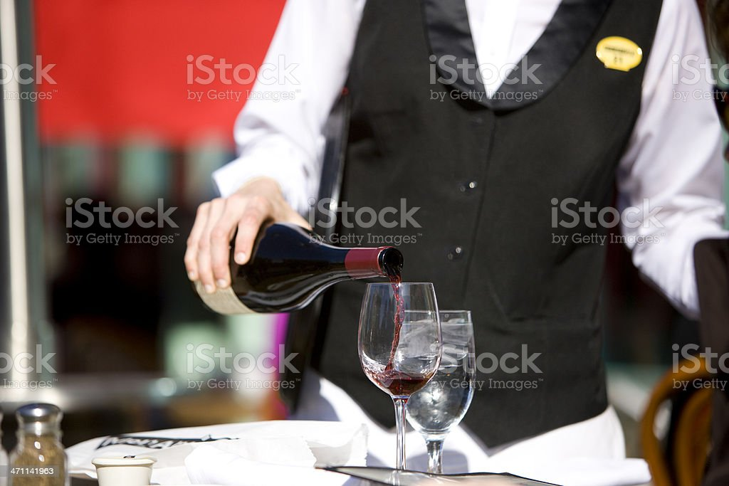 Waiter pouring wine stock photo