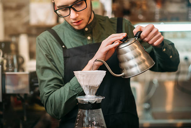 waiter pours hot boiled water in a coffee pot - バリスタ ストックフォトと画像