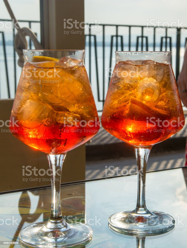Waiter prepared the Aperol Sprits summer cocktail with Aperol, prosecco, ice cubes and orange in wine glass, ready to drink on sunny terrace - foto stock