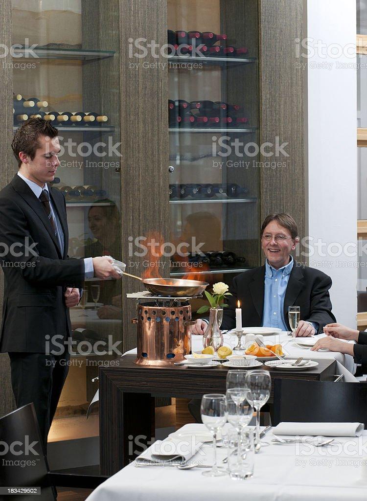 waiter preparing flambe crepes at restaurant table stock photo
